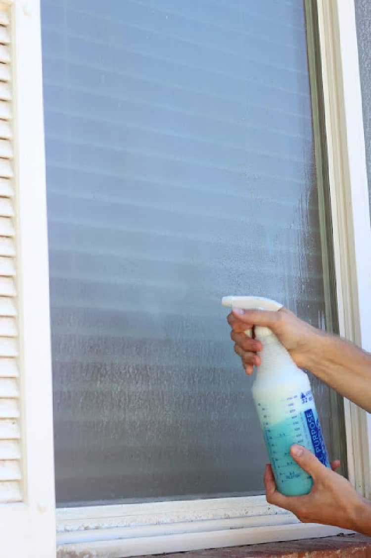 Person spraying windows with hard water stains with a diy window cleaning solution