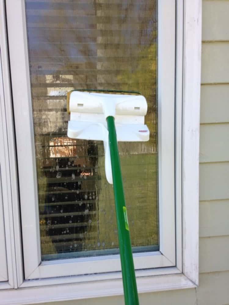 Washing windows with a long-handled brush