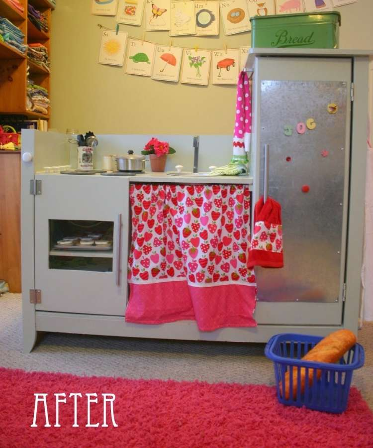 Changing table converted into a custom kids kitchen with strawberry curtains and kitchen magnets.