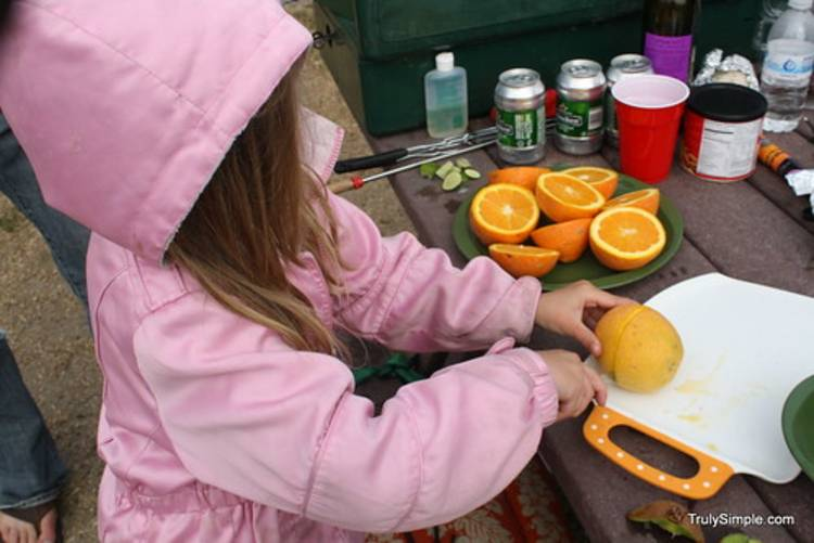 cold-weather-camping image of a child in a jacket cutting an orange on a cutting board at a campsite picnic table