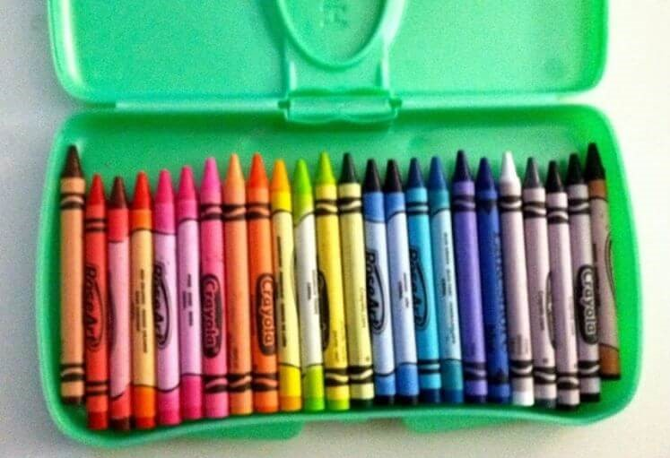 Crayons in an empty travel baby wipes container