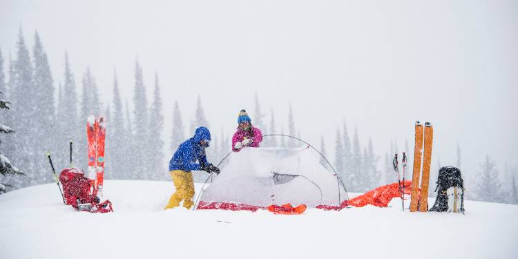 cold-weather-camping image of a campsite in the snow with two campers and their gear around a tent