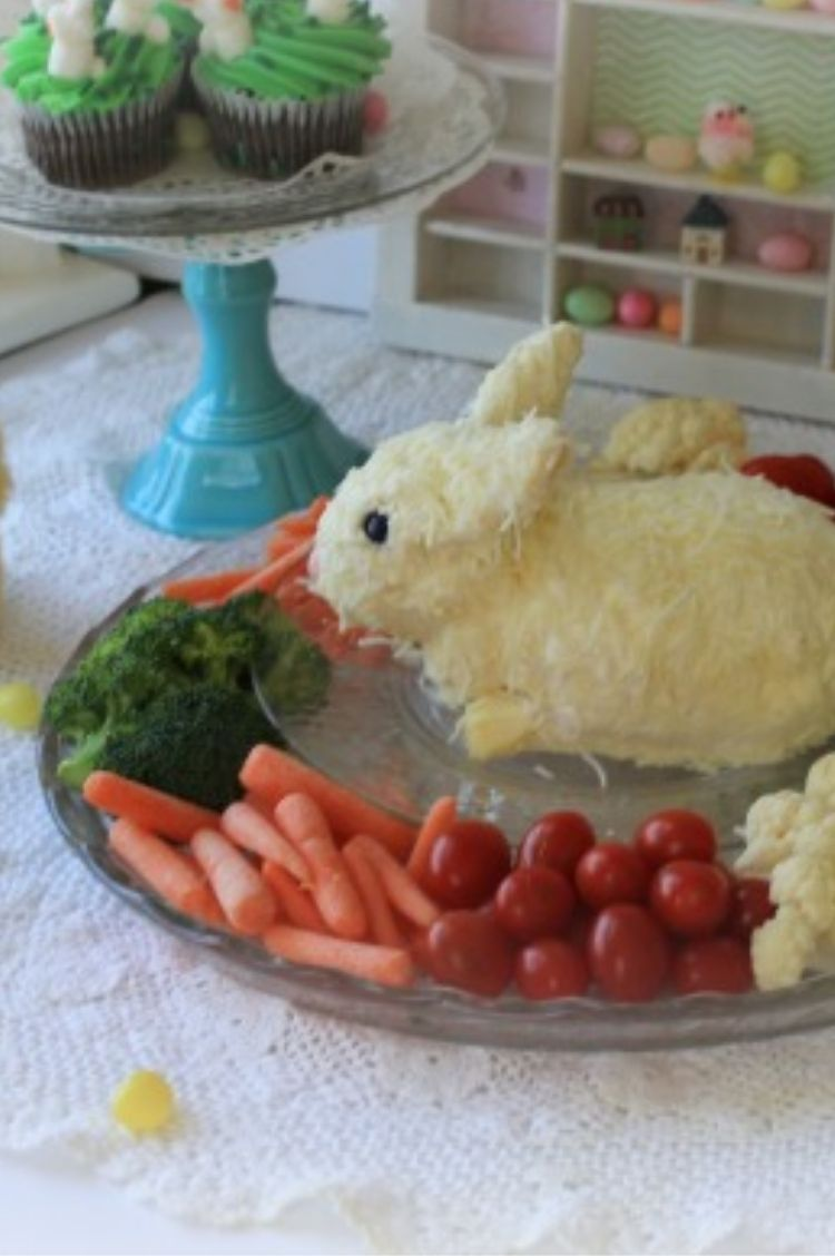 Classic cheese ball recipe made into the shape of a bunny surrounded by veggies on a plate