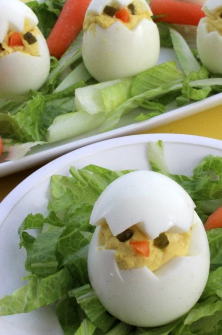 Deviled eggs cut in half and filled to look like a cracked egg, use small edible pieces of carrots or peppers to make faces inside the filling