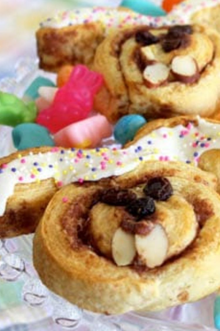 Cinnamon rolls pulled apart and placed into the shape of bunny faces with frosting and fruits to make faces on top
