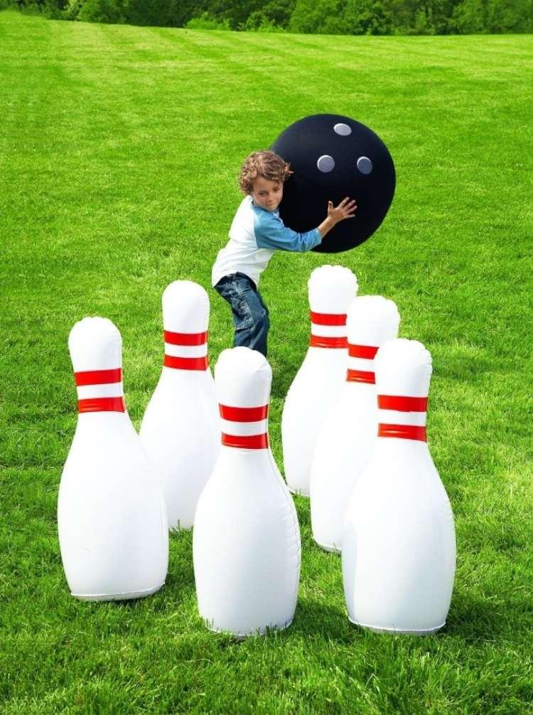 Backyard ideas: Child lawn bowling on green grass
