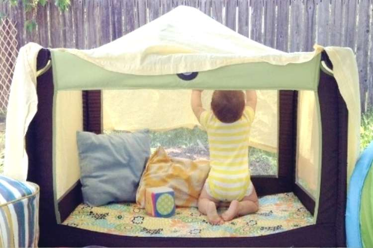 baby in playpen with cover for shade