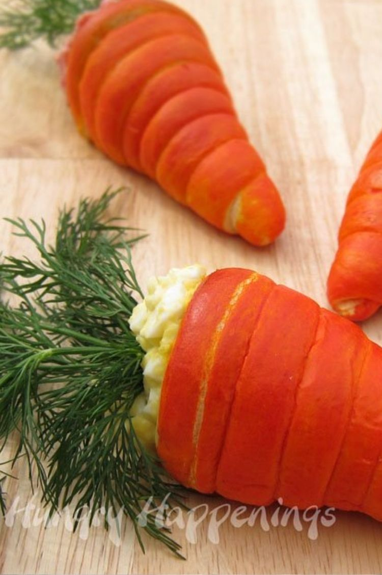 Crescent rolls dyed orange and wrapped around to form the look of a carrot, stuffed with egg salad