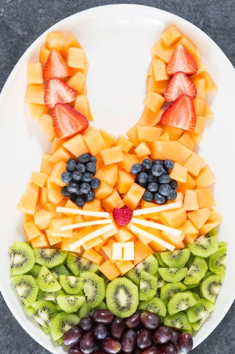 Easter party Fruit arranged in the shape of a Easter bunny face using strawberries, blueberries, cantaloupe, and kiwi
