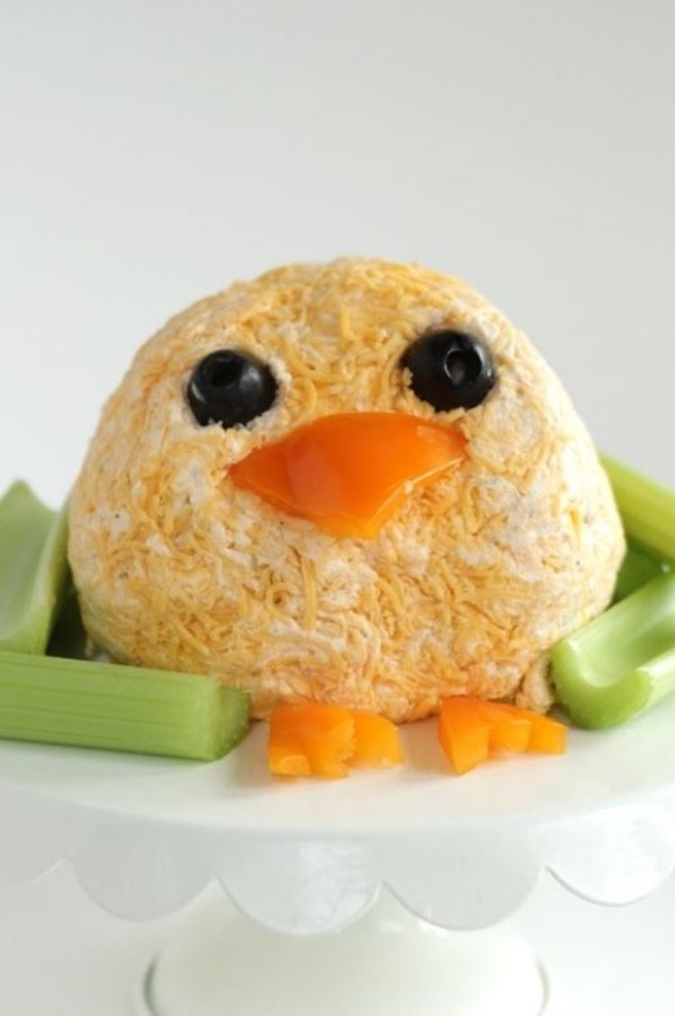 Edible cheese ball made into the shape of Easter Chick with olives for eyes and peppers cut into a beak and feet shapes