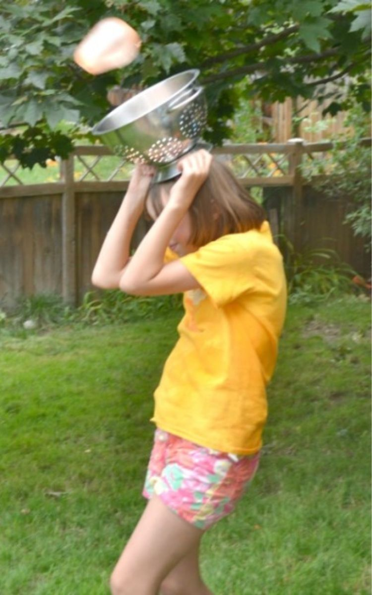 Girl carrying colander on her head for a water balloon game