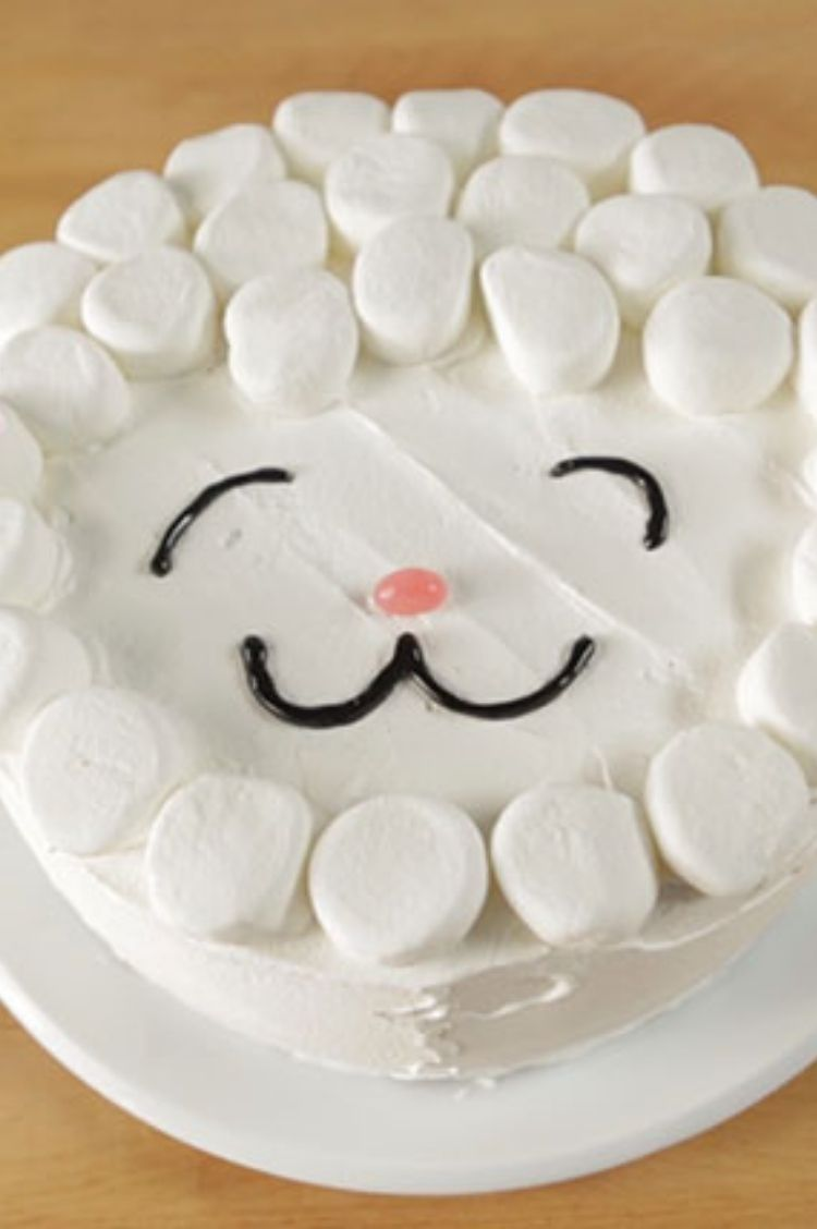 White frosted cake with large marshmallows along the sides and black icing for a smile and eyes
