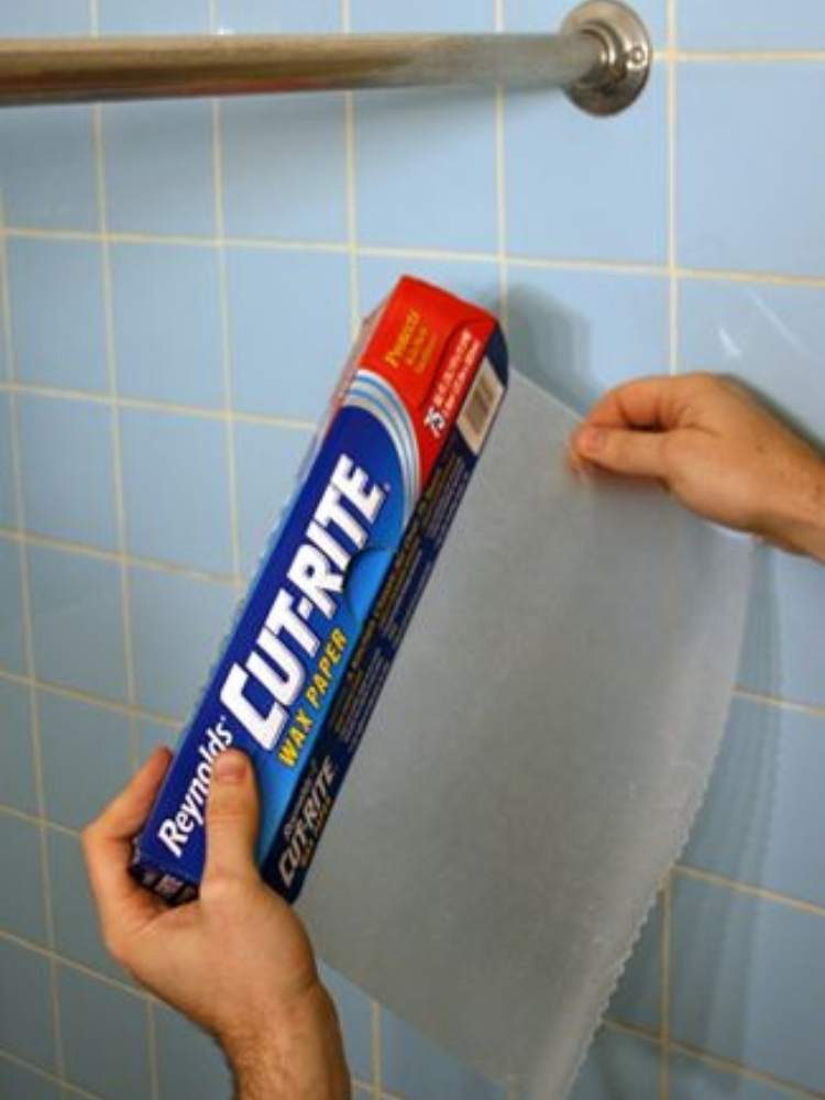Picture of wax paper being used to clean shower curtain rod