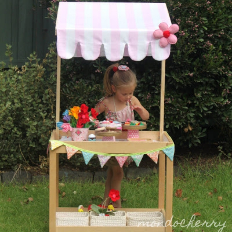 Little girl standing at repurposed changing tables transformed into outdoor play table with pink canopy