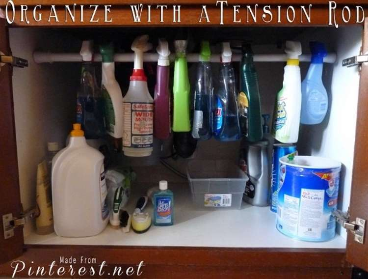 OneCrazyHouse How to Organize Kitchen Cabinet under sink open, revealing a tension rod holding all spray cleaning bottles.
