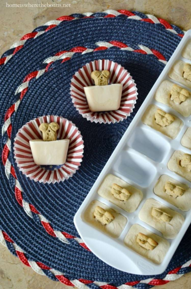 Frozen yogurt dog treats with bone shaped biscuits poking out in cupcake wrappers next to ice cube tray full of dog treats.