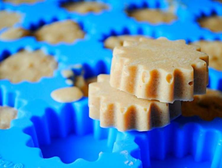 Two peanut butter and coconut oil frozen dog treats resting on bold used to create shape pointy sided round shape.
