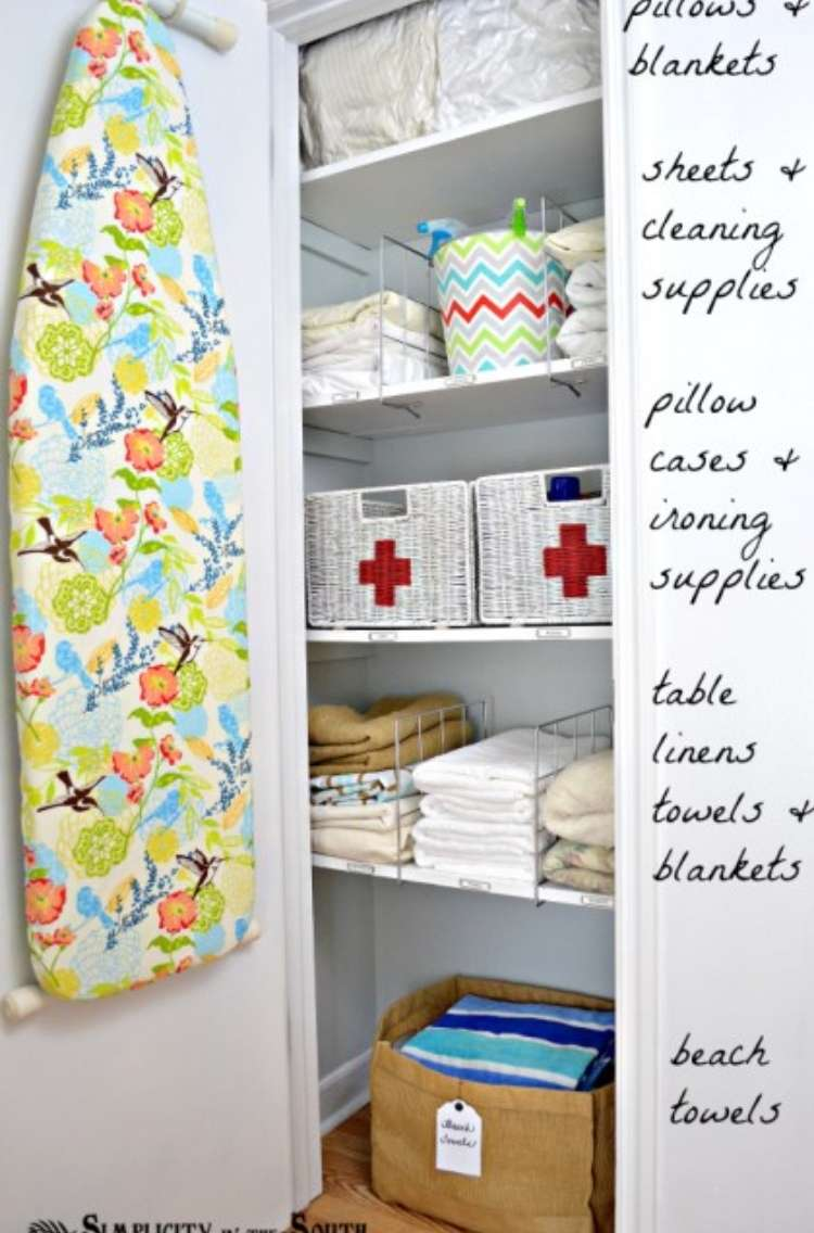 Open linen closet with ironing board hanging on inside of the door, and neat shelves inside. Container with beach towels on the lowest shelf for easy access