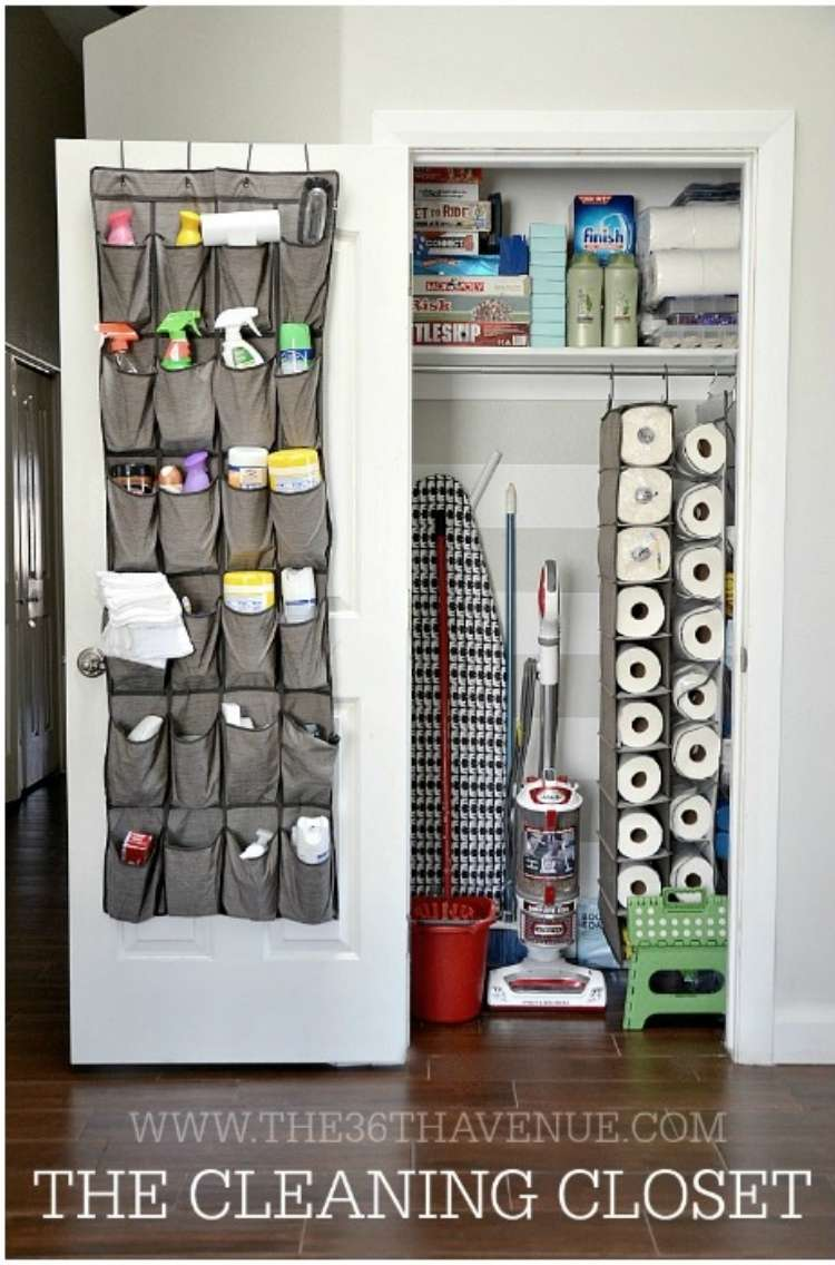 Open linen closet with shoe holder repurposed to hold cleaning supplies on the inside of the door and shoe holders hanging inside holding papertowels