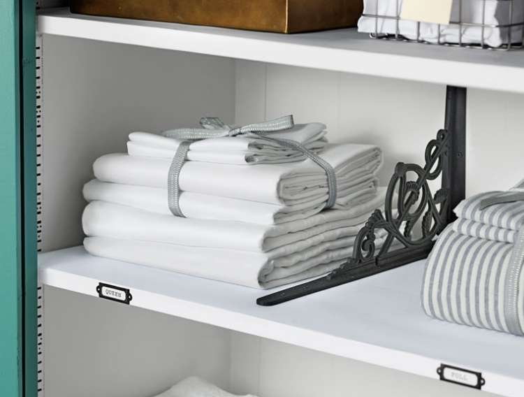Towels folded and neatly stacked on a shelf with a label on the front of the shelf. Divider sectioning off area for towels, with another compartment with linens next to it.