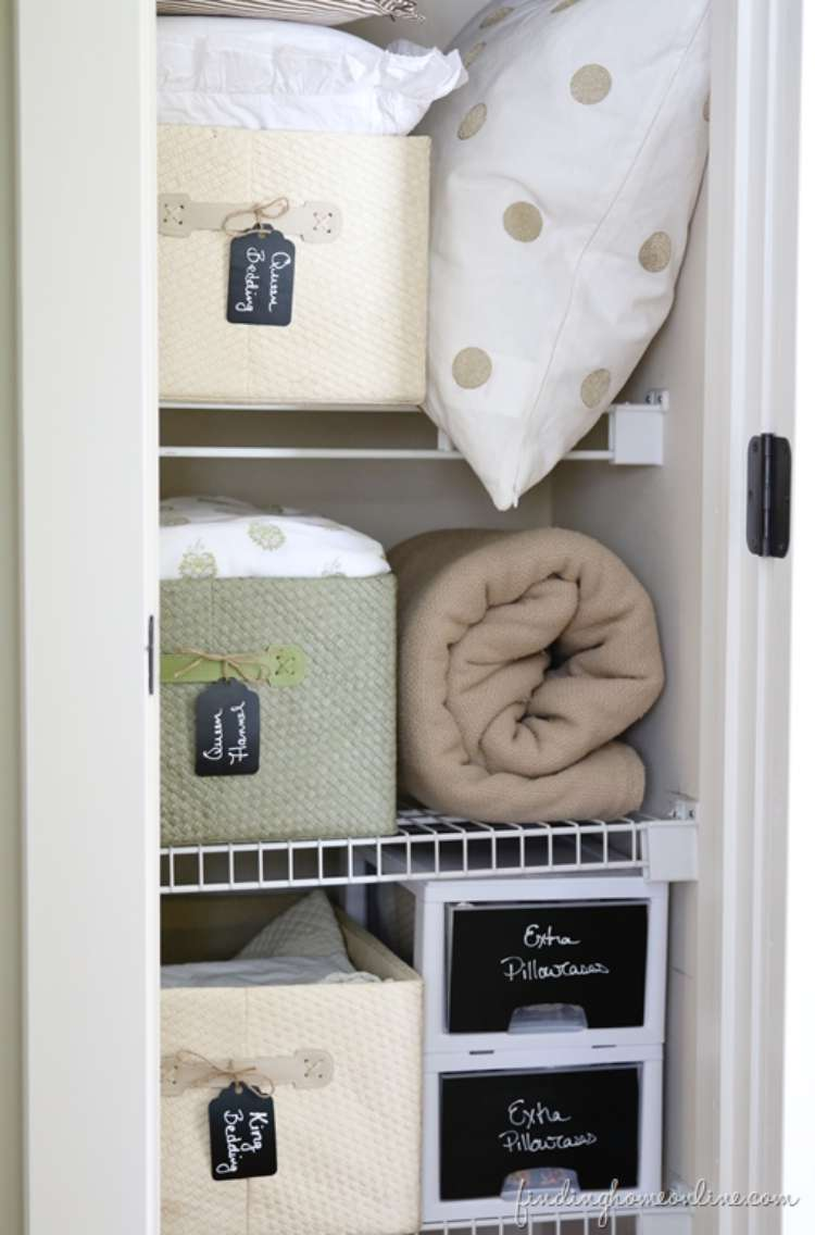 Onecrazyhouse Linen Closet Organization Linen closet with deep cloth drawers with labels hanging from handle with pillows and blankets stack beside drawer on each shelf in linen closet