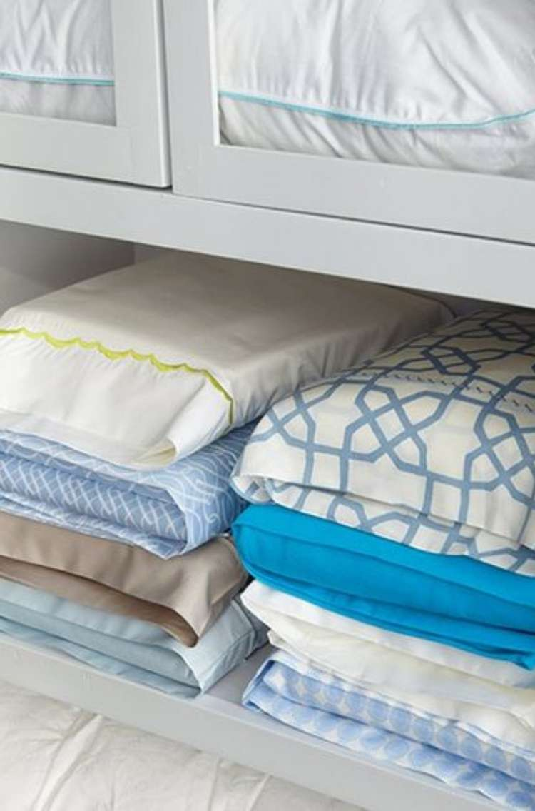 Linen closet with 8 sheet sets stored inside corresponding pillowcase stacked neatly on a shelf