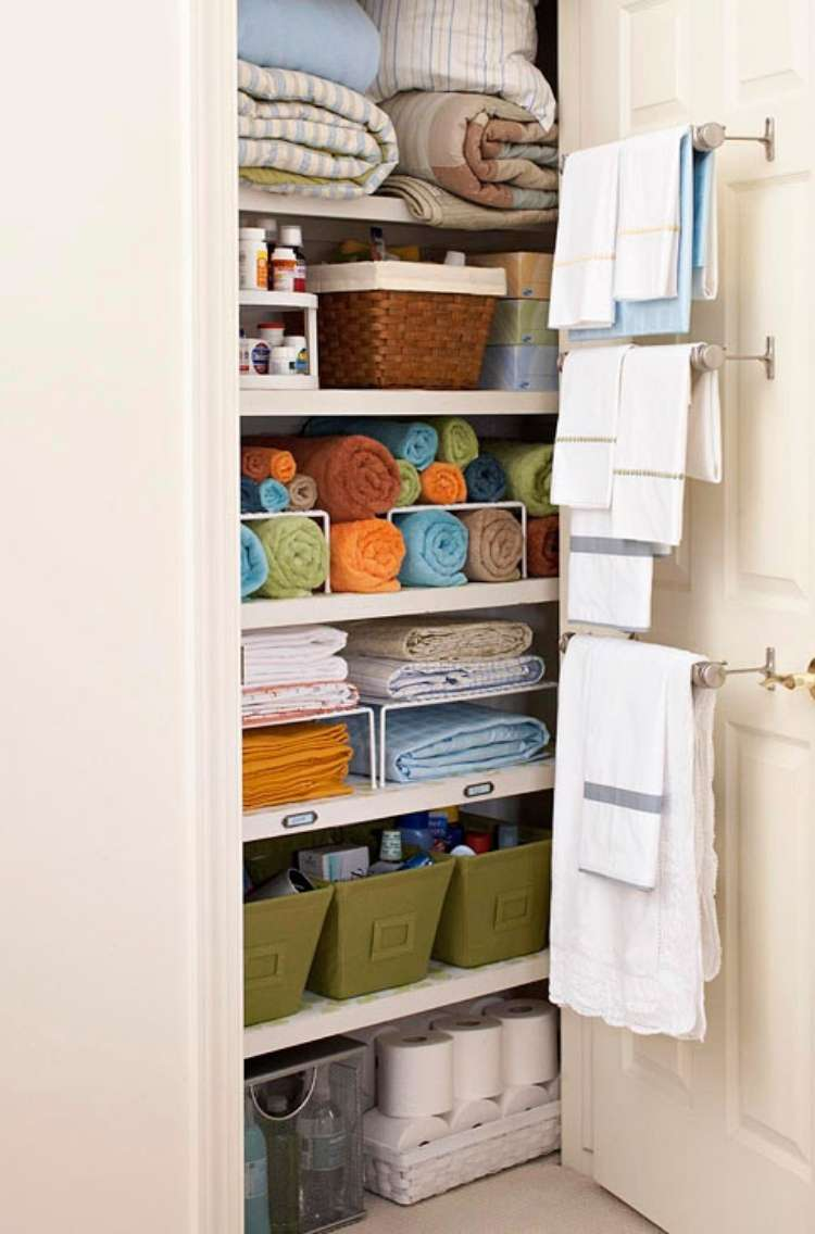 Onecrazyhouse Linen Closet Organization linen closet open to show neatly folded linens with towels hanging from towel racks attached to inside of the door