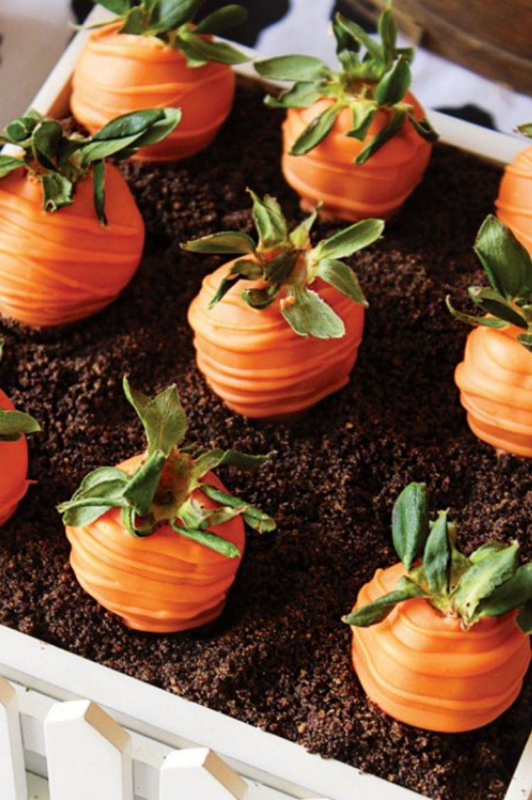 Orange Chocolate covered strawberries made to look like carrots in a crumbled cookie mix bed