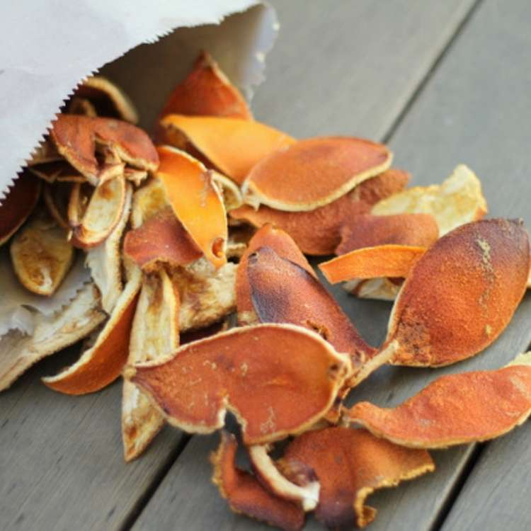 Orange Peel Uses - Dried orange peels for kindling pouring out of brown paper bag