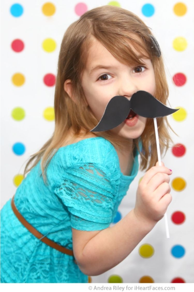 photo booth props for parties - girl hold a mustache prop for a photo booth