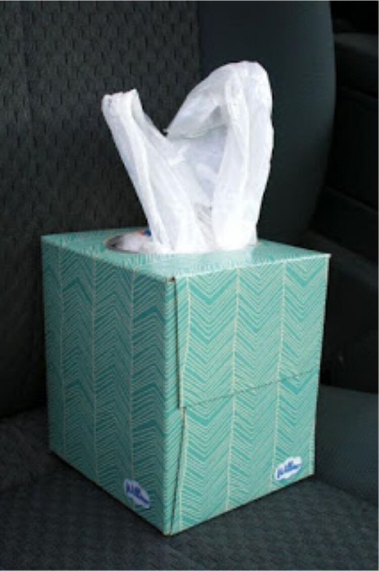 Tissue box filled with plastic sacks for an easy car storage hack