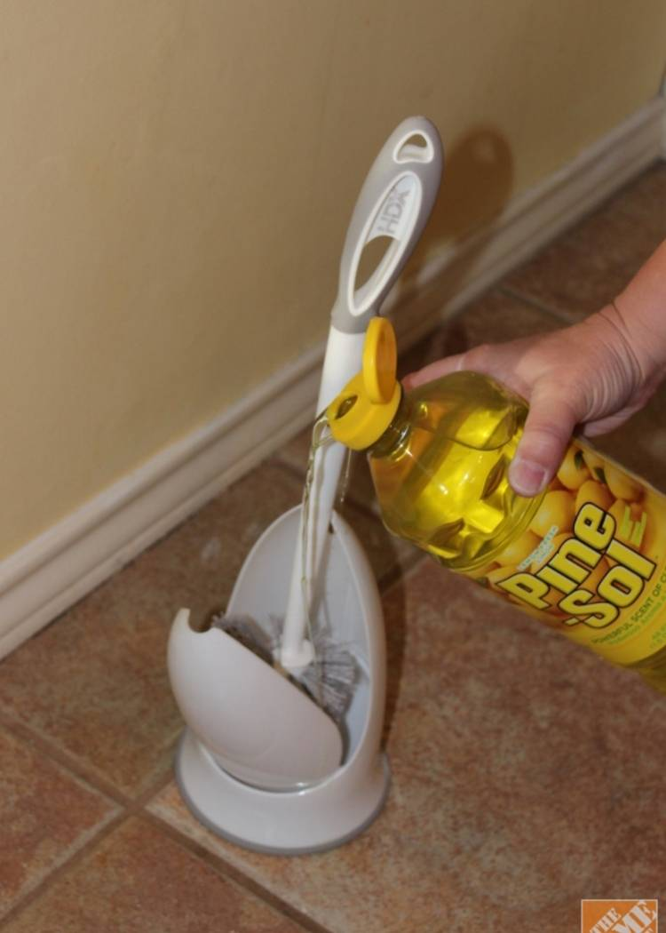 pouring disinfectant on a toilet bowl brush holder