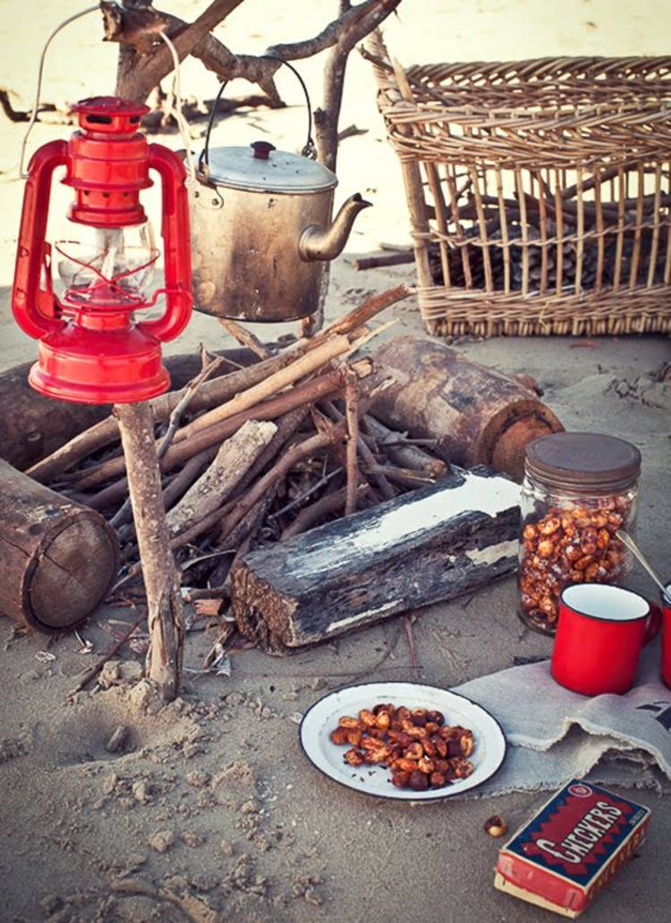 cold-weather-camping image of a campfire, lantern, a plate with food, a tin mug, and a jar of food on the sand