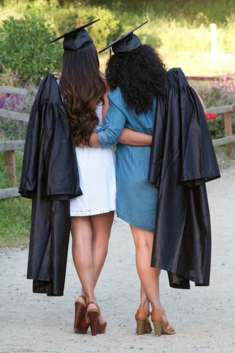 senior picture ideas for girls - 2 girls casually adorned in graduation caps and gowns facing away from the camera