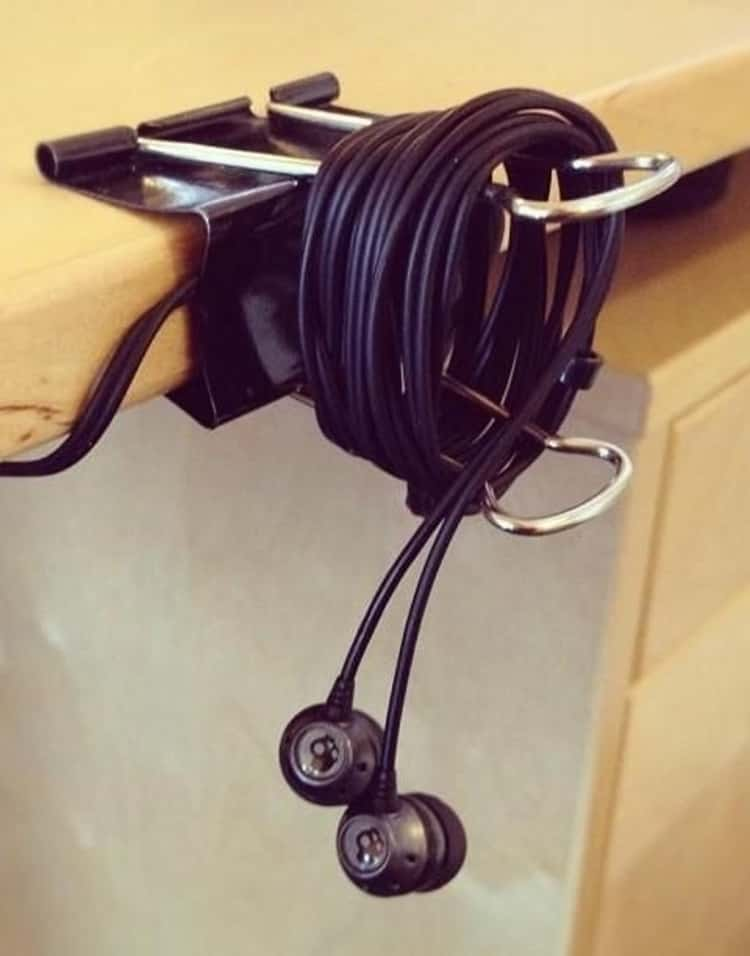 binder-clip-earbuds holder clipped to the edge of a desk
