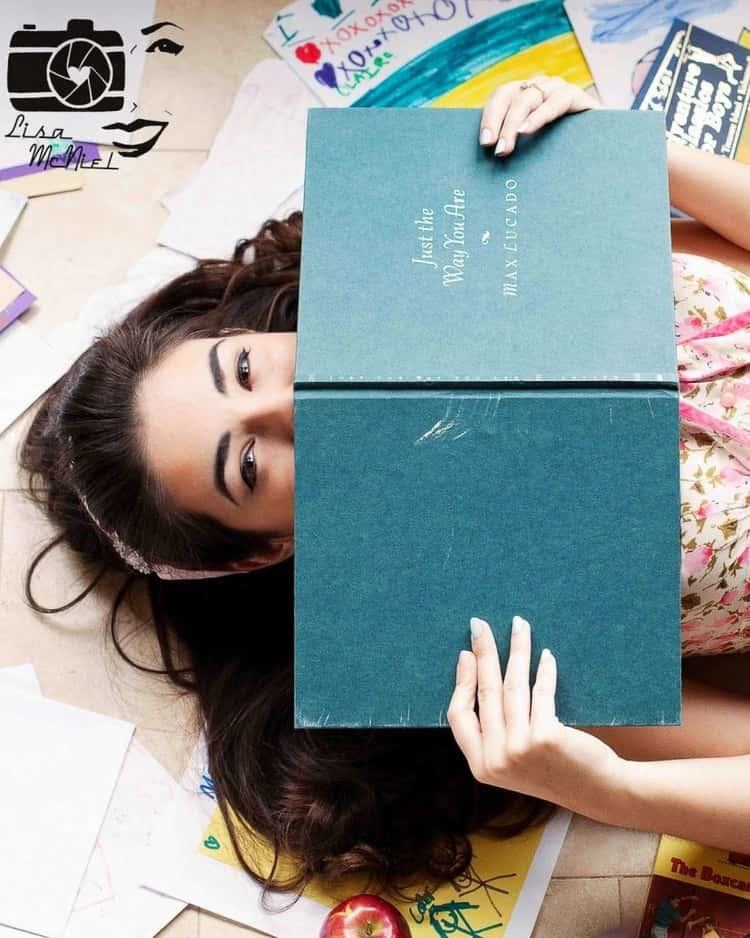 senior picture ideas for girls - upper-half body shot of girl lying down with open book partially covering her face from the nose downwards