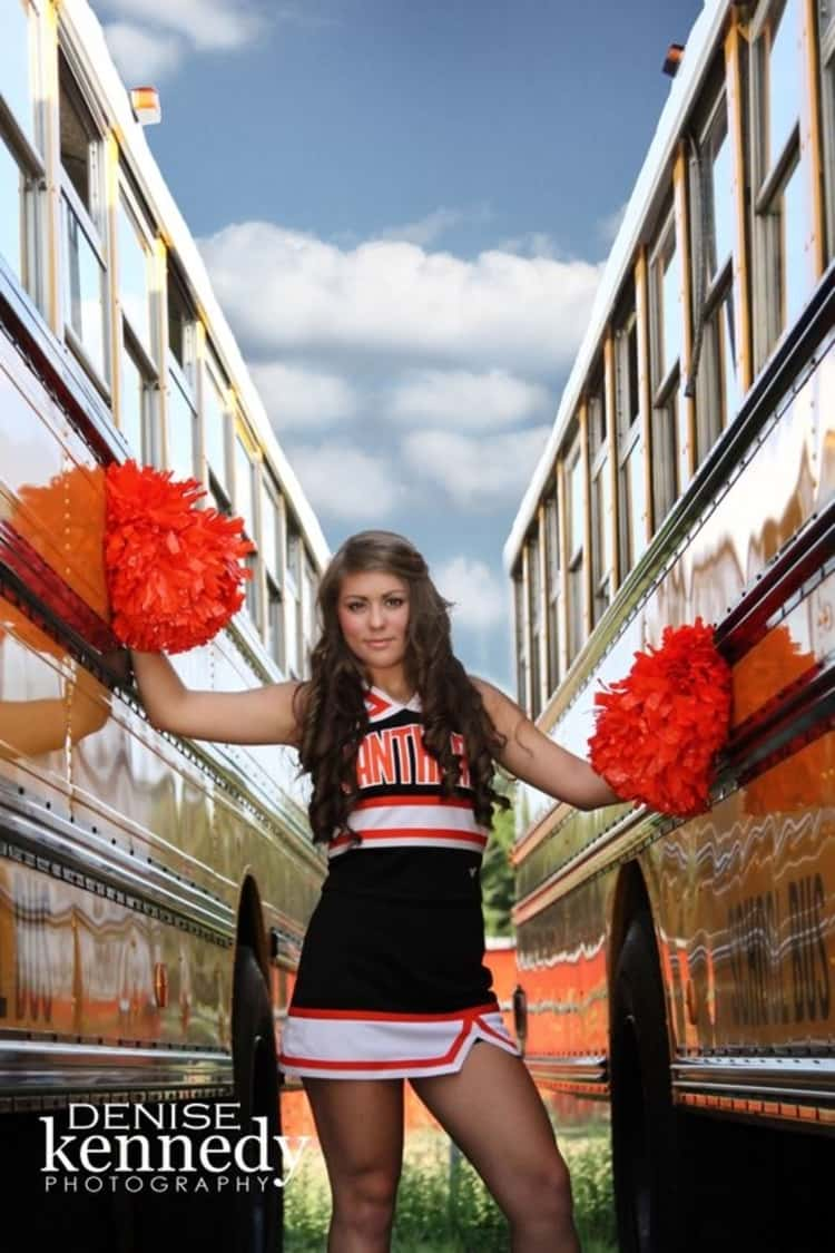 senior picture ideas for girls - cheerleader holding pompoms in her hands while standing between 2 buses