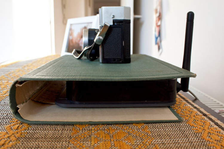 hHdden storage idea - a book cover being used to disguise a router and hide it from sight.