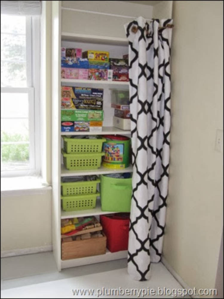 Picture of ots of toys and baskets on shelves - a decorative curtain is being used to hide them.