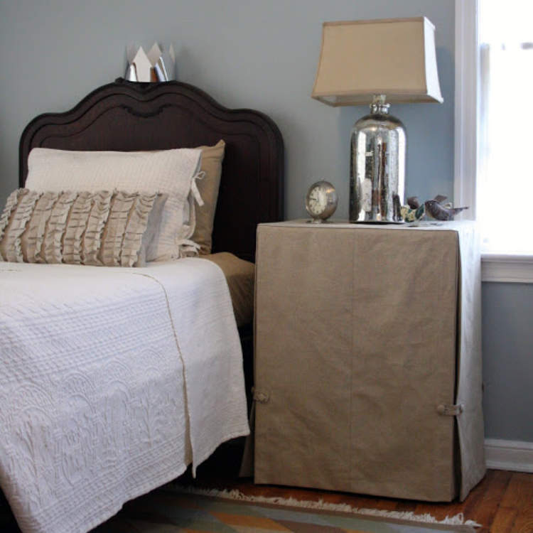 Hidden storage created by hiding a bedside table under a fabric skirt.