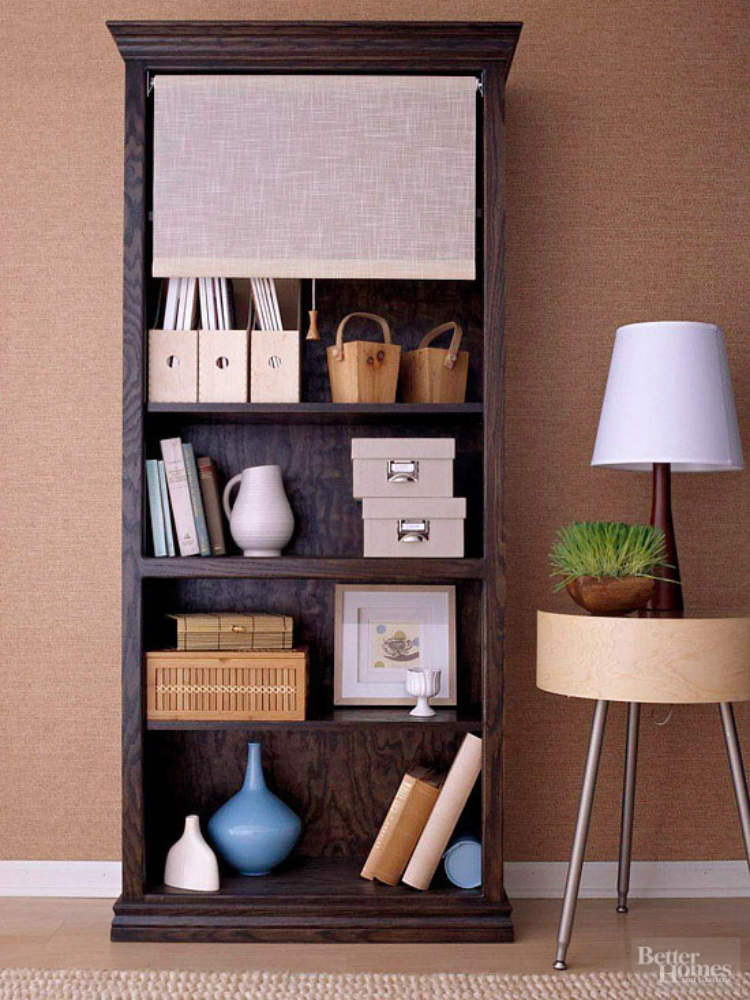 Storage ideas, including a roll down shade hiding clutter on a bookshelf