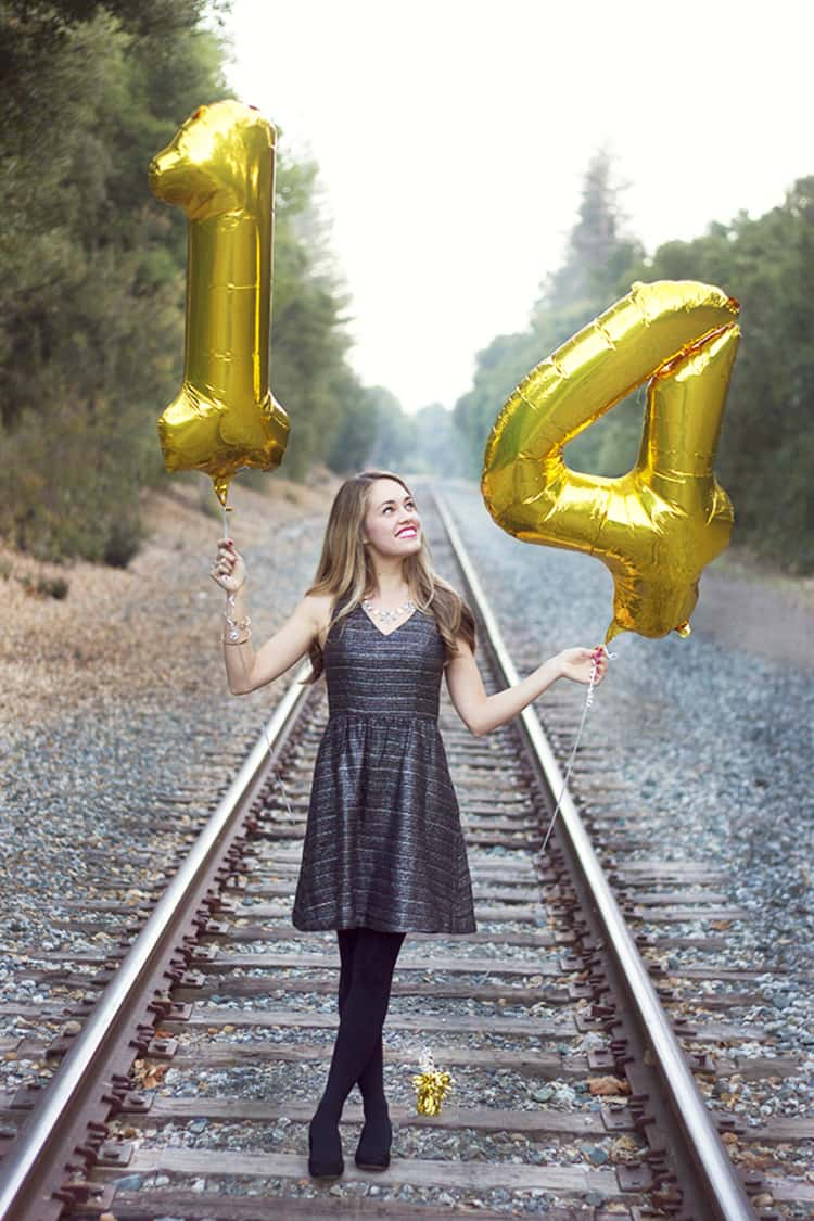 senior picture ideas for girls - girl standing on railtrack holding up 2 number-shaped balloons in her hands