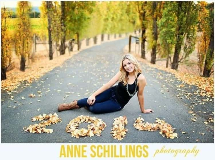 girl seated on road with fall leaves spelling the year 2014 in numbers