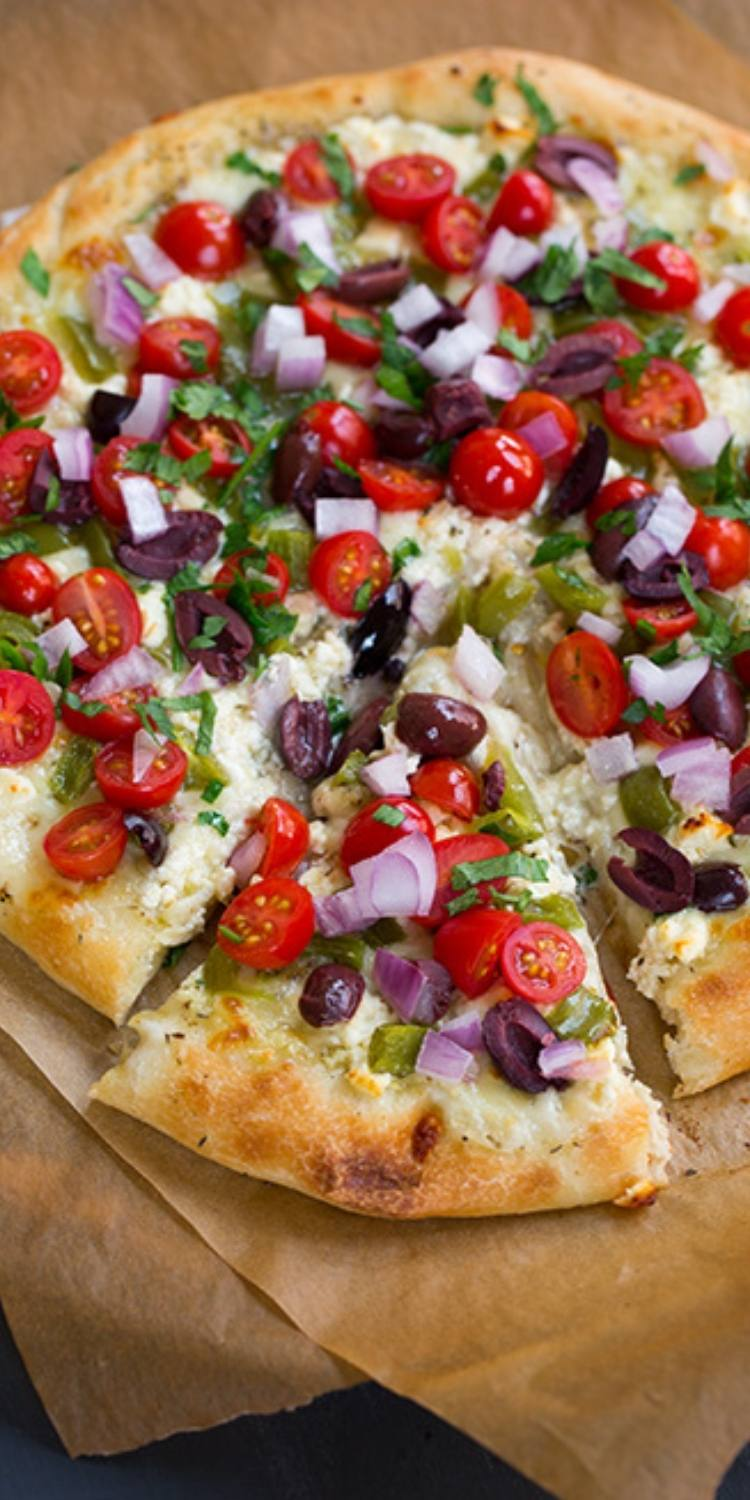 Greek salad pizza ideas. Tomatoes, onions, olives, and basil atop a flatbread pizza crust.