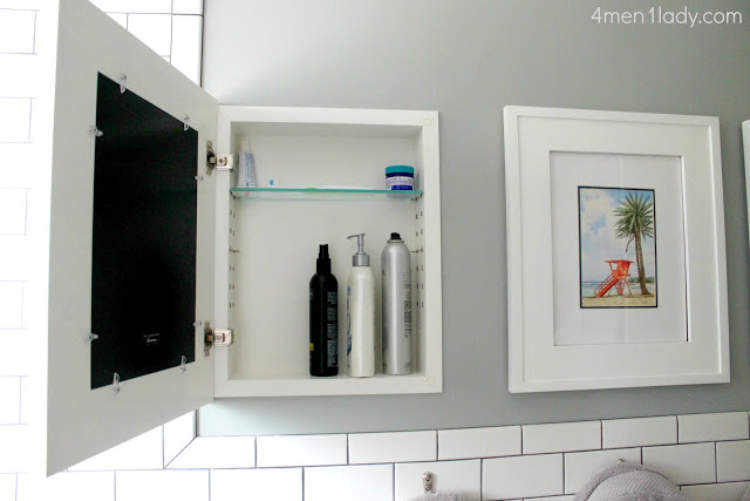 Hidden storage idea for the bathroom - including a built in cabinet concealed by framed art.