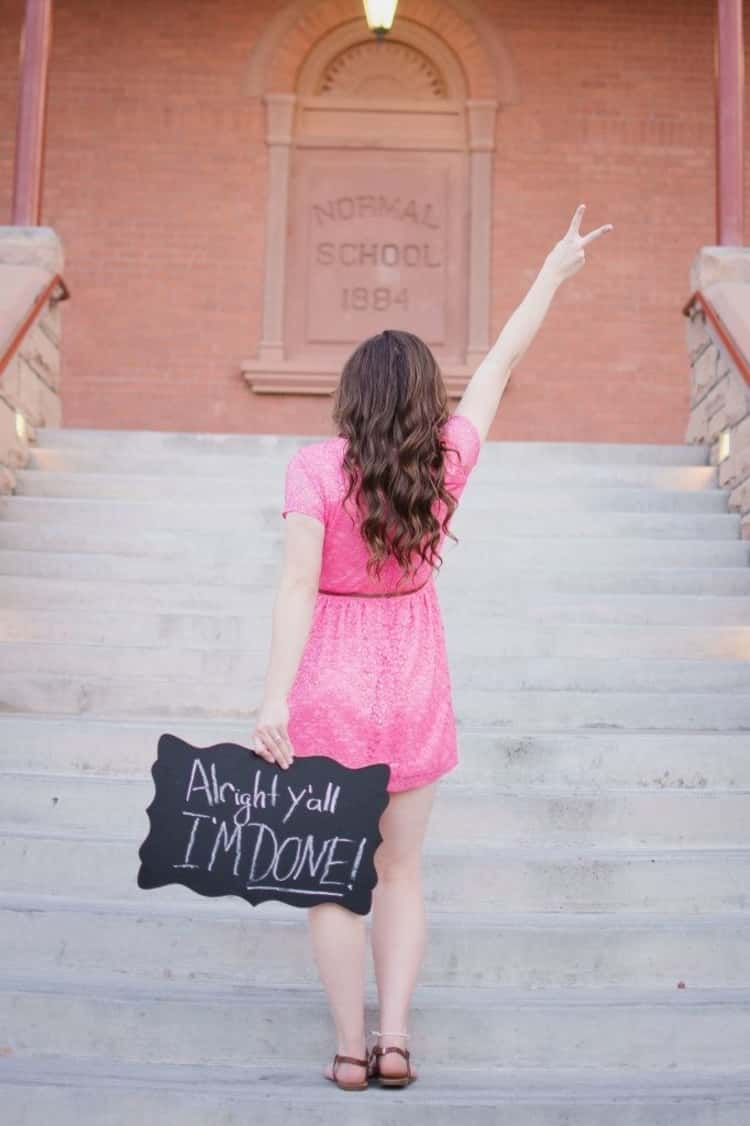 senior picture ideas for girls - girl in pink dress facing away from camera and holding chalkboard sign behind her in left hand written 'Alright y'all, I'M DONE!' while her right hand is held up in a victory sign