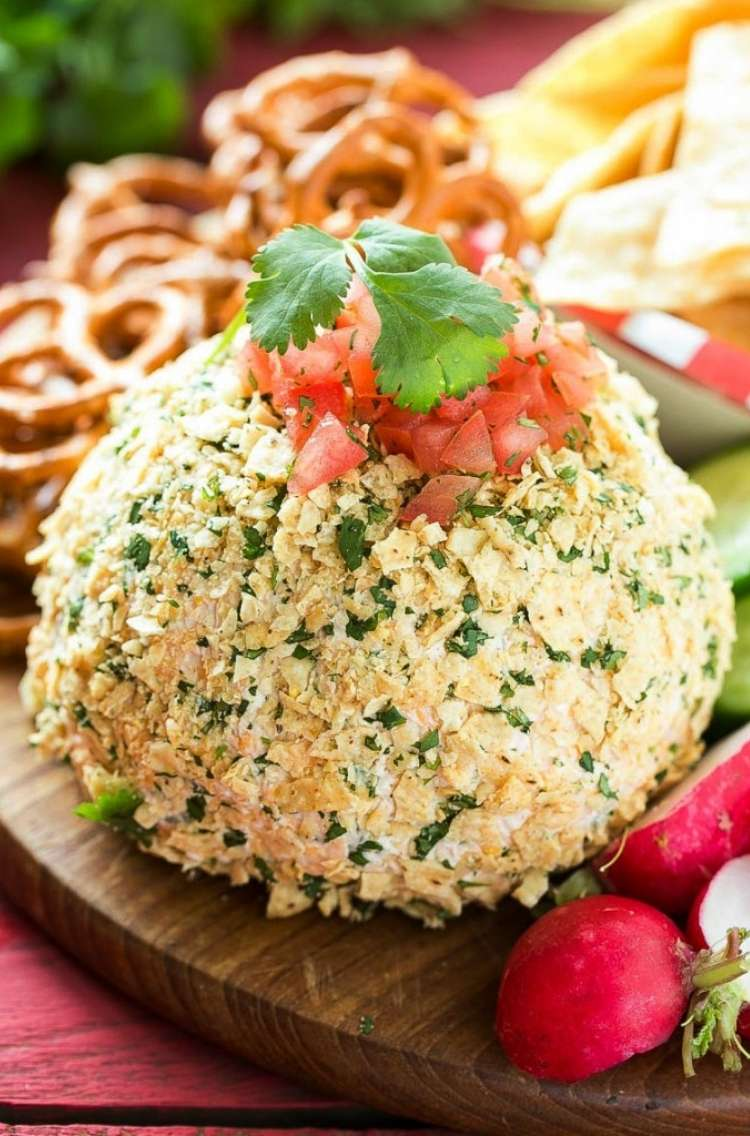 jalepeno cheddar cheese ball topped with diced tomatoes and a green leaf garnish