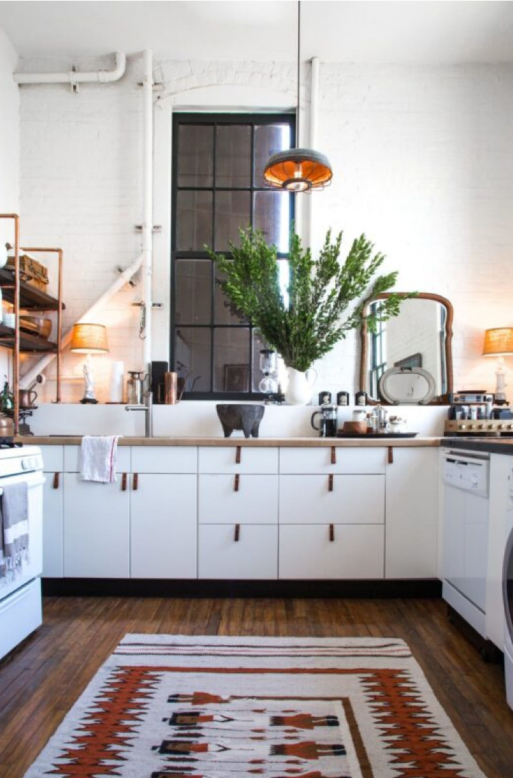 apartment decorating with white kitchen with a rug on the floor and pulls on the cabinets