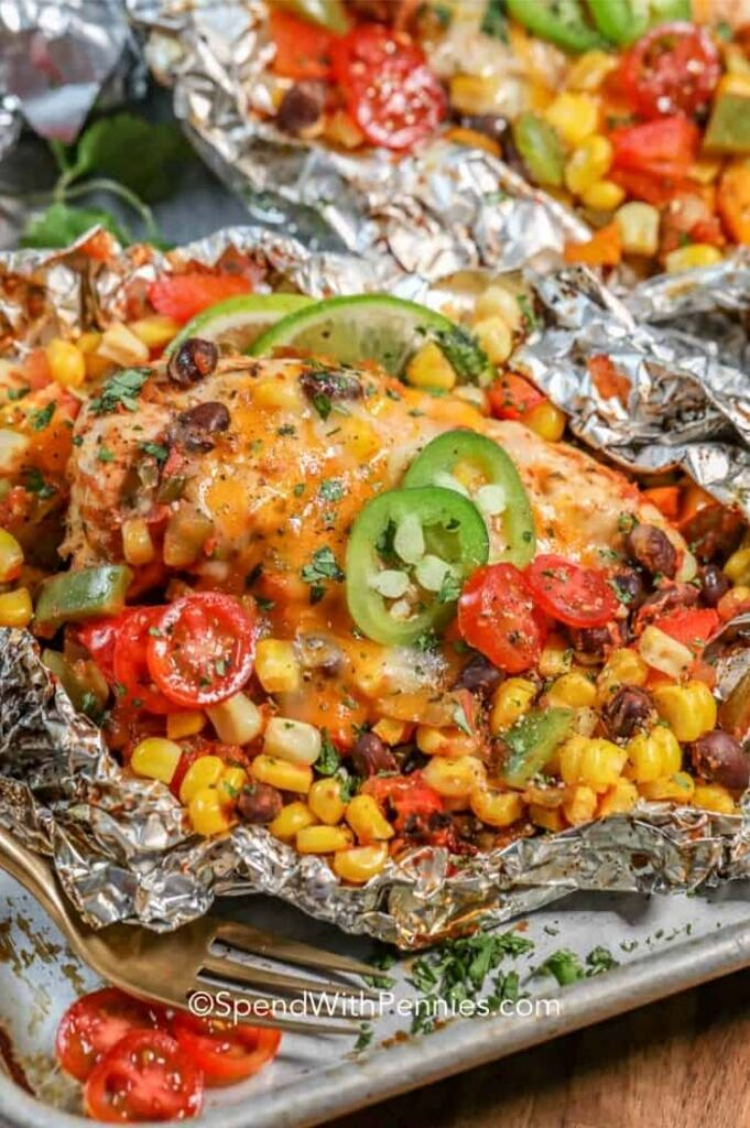 foil packet with chicken, corn, beans, and veggies cooked on it