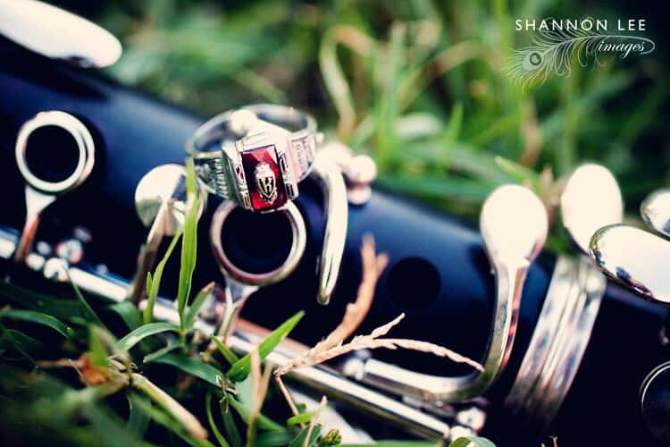 musical instrument placed in the grass with a class ring placed on top it it
